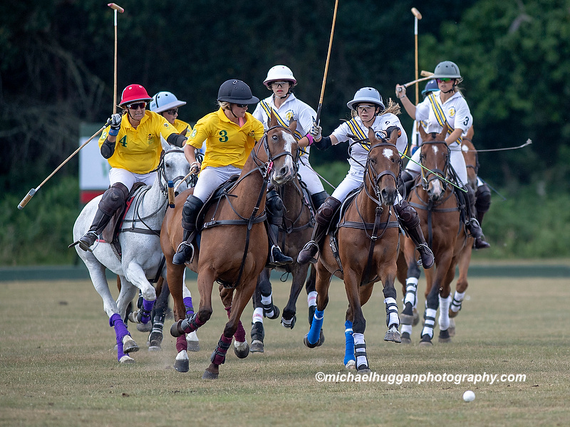Lucy Bowman for Maiz Dulce (yellow shirt) is chased by Beanie Bradley of Coombe Place Polo Team