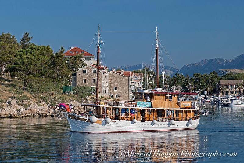 Small cruise boat leaving Makarska harbour